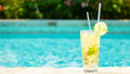 Mojito cocktail at the edge of a resort pool.  Concept of luxury Royalty Free Stock Photo
