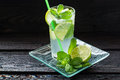 Mojito cocktail in a highball with rum lime mint and soda on glass tray Royalty Free Stock Image