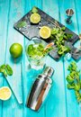 Mojito cocktail with lime and mint in highball glass on a blue wood table. Drink making tools and ingredients for cocktail Royalty Free Stock Photo
