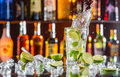 Mojito drink on bar counter cocktail with splash served with blur bottles background Royalty Free Stock Photos