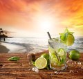 Mojito drink on beach with sunset served wooden planks blur in as background Stock Photo