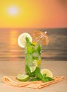 Mojito lemon and napkin with umbrella a on a table against the sunset Royalty Free Stock Photos