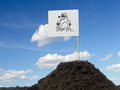 Mole mound with white flag showing icon affixed over blue sky Stock Photo