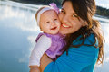 Mom and baby daughter smiling by a lake holding girl Royalty Free Stock Photos