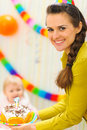 Mom carries birthday cake to baby Stock Photo