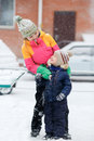 Mom with child playing outdoors at street in winter during snowfall. Royalty Free Stock Photo