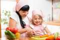Mom and child preparing healthy food at kitchen daughter Stock Photography