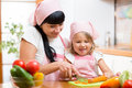 Mom and child preparing healthy food at kitchen mother Stock Photography