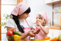 Mom and child preparing healthy food at kitchen mother Stock Images