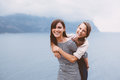 Mom with children walking outdoor and her teenage daughter hugging and smiling together over blue sea view Royalty Free Stock Photo