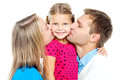 Mom and dad kissing their beautiful kid Stock Photo