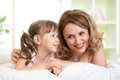 Mom with daughter converse lying on bed at home Royalty Free Stock Photography