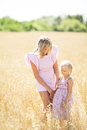 Mom and daughter in the field. Mom and daughter of a blonde in pink dresses. Royalty Free Stock Photo