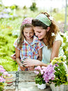 Mom and daughter have fun in the work of gardening a greenhouse Royalty Free Stock Images
