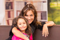 Mom and daughter posing happily indoors in sofa smiling to camera Royalty Free Stock Images