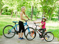 Mom and daughter ride bikes in the park Royalty Free Stock Photo