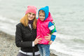 Mom and daughter in warm clothes hugging each other on the beach in cold weather and with a smile look Royalty Free Stock Photo