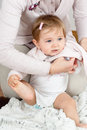 Mom dressing up baby cute girl getting dressed by while holding the foot with the hand Stock Images
