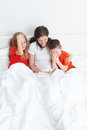 Mom eading a book having fun reading in bed for her childs before sleep Stock Photos