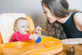 Mom feeds the baby puree healthy and natural baby food vegetables broccoli child sitting on highchair at table Royalty Free Stock Photo
