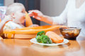 Mom feeds the baby soup healthy and natural baby food vegetables carrots cabbage broccoli child sitting on highchair at Royalty Free Stock Photo