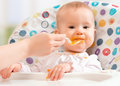 Mom feeds funny baby from spoon a Stock Image