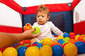 Mom hand giving balls to baby mother colorful his son in playpen Stock Images