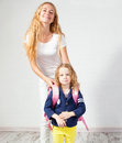 Mom helps her daughter get ready for school mother support child to wear a backpack Stock Images