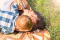 Mom and her little son indulge and have fun on a plaid on the gr Royalty Free Stock Photo