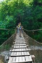 Mom and his son tourists cross the mountain river on suspension bridge Royalty Free Stock Photo