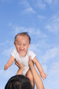 Mom hold baby up mother is holding against blue cloudy sky is very happy and excited Stock Photography