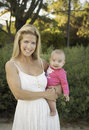 Mom holding happy baby girl with blue eyes blond hair and white dress holds a cute smiling with big blue eyes and wearing pink Royalty Free Stock Images