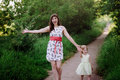 Mom keeps daughter s hand and walks the walk on the nature in sunset light motherhood child family Stock Photos