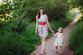 Mom keeps daughter s hand and walks the walk on the nature in sunset light motherhood child family Royalty Free Stock Photo
