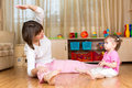Mom and kid doing exercises sitting on the floor in home interio Royalty Free Stock Image
