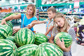 Mom with kids choose watermelon at grocery store Royalty Free Stock Photo
