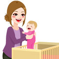 Mom picking baby from crib beautiful young girl Royalty Free Stock Photo