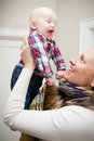 Mom playing with baby a mother holding up her young son they are happily each other Royalty Free Stock Photography