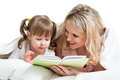 Mom reading a book to kid lying in the bed Royalty Free Stock Photo