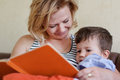 Mom reading tales for son from book Stock Photo