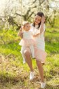 stock image of  Mom rolls the baby on a swing in the flowering gardens or park. Mother`s Day, March 8, spring mood