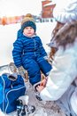Mom shoes her son in winter shoes after skiing. Little boy 3-6 years old, sitting on a bench, in the winter in the city Royalty Free Stock Photo
