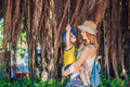 Mom and son on Vietnam travelers are on the background Beautiful tree with aerial roots