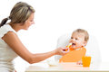 Mom spoon feeding her happy baby girl Royalty Free Stock Photo