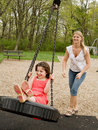 Mom Swinging Daughter Stock Image