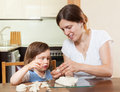 Mom teaches malekuyu girl sculpt dough figurines in the room Royalty Free Stock Image