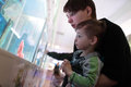 Mom tells her son about fish at an oceanarium Stock Photos