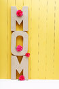 Mom text letters with carnations on yellow wooden background pink Royalty Free Stock Photography