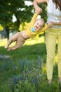 Mom throws baby in her arms up the park Stock Image