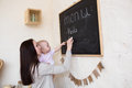 Mom and Toddler Daughter playing menu planning write to blackboa Royalty Free Stock Photo
